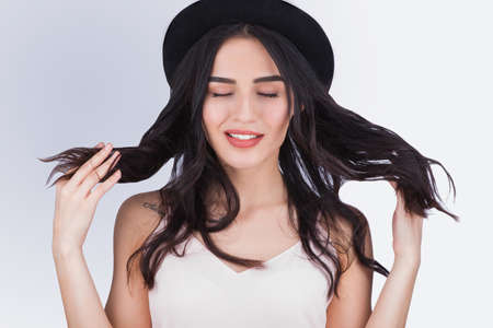 millennial: Gorgeous young woman in black hat playing with her hair on a gray background