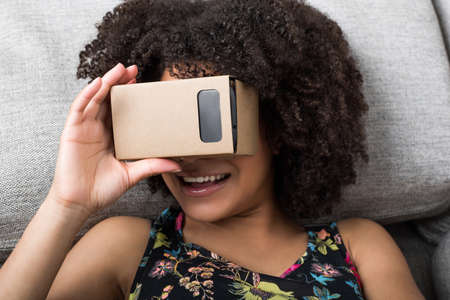 simulator: Young smiling woman using virtual reality device cardboard vr at home Stock Photo