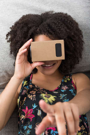 simulations: Young woman using virtual reality device cardboard vr Stock Photo