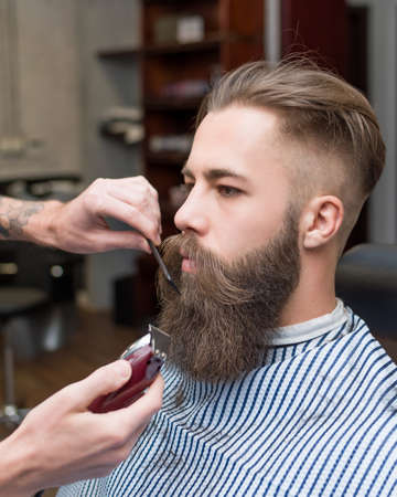 haircut: Handsome man with a long mustache in barbershop Stock Photo