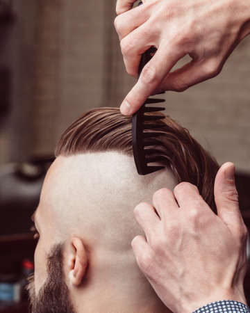 undercut: Handsome man with a long beard and undercut in barbershop Stock Photo