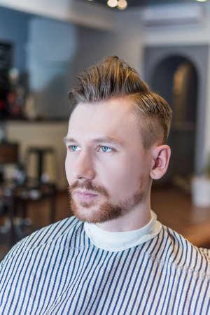 undercut: Handsome man with undercut in barbershop