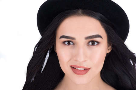 millennial: Closeup headshot of a stylish beautiful girl in black hat over white background Stock Photo