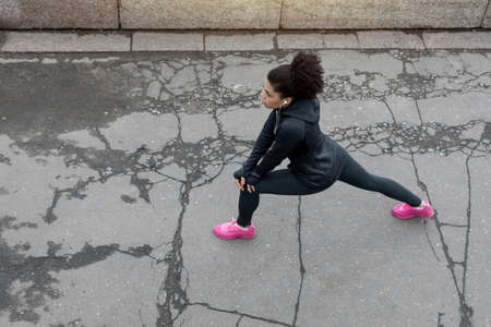 athleticism: Overhead view of young female runner prepares for workout on city street Stock Photo
