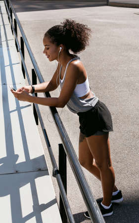 1 person: Sporty woman standing by railing, using mobile phone Stock Photo