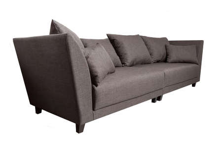 Modern grey fabric sofa with pillows isolated on white background. Side view. Strict style furniture