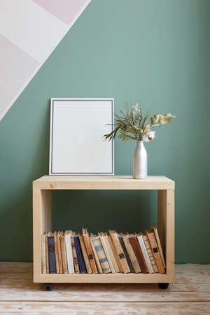 Green plant with a white flower on a bookcase with old books and a frame with a copy space on it. Cozy room with wooden floors and green walls Foto de archivo