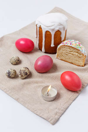 Easter cakes and colorful eggs on festive Easter table with lighted candle.