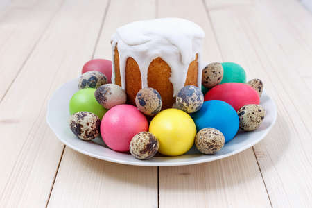 Easter cake and colorful eggs on a plate on a wooden table .