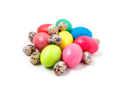 Colored Easter eggs lie on a white background. Yellow, red, green, blue eggs and quail eggs folded together in a pile Reklamní fotografie