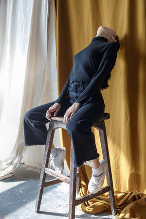 lonely pretty brunette girl in black turtleneck and jeans sits on stool, stretches and bends her head back in emty room