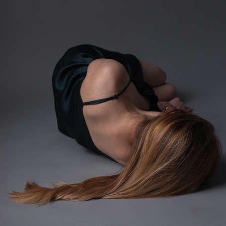 girl in dress lies on floor with head turned away. Depression, anxiety concept 版權商用圖片