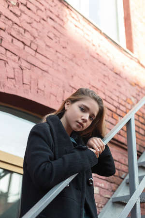 Young girl in black coat standing on stairs with brick wall on background. Concept of loneliness.