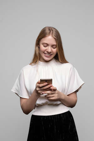 young pretty blond girl with long hair smiling and using cell phone isolated on gray background. Modern communication