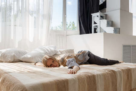 cute blonde girl with long hair in striped shirt and black pants lies in bed at studio face down and looks at camera Foto de archivo