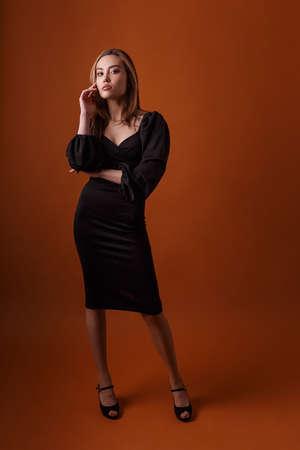 elegant model wearing black dress and highheel shoes posing on orange background