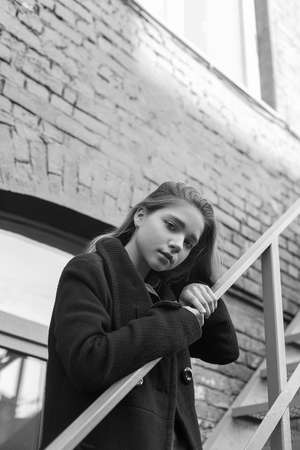 Young girl in black coat standing on stairs with brick wall on background. Concept of loneliness. Black and white image