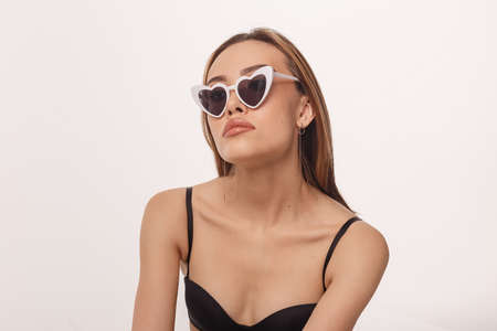 sexy asian woman posing in black lingerie, sunglasses on white studio background Banque d'images