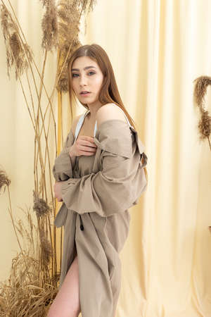 pretty woman in beige raincoat on pastel fabric background. fashion photo shoot