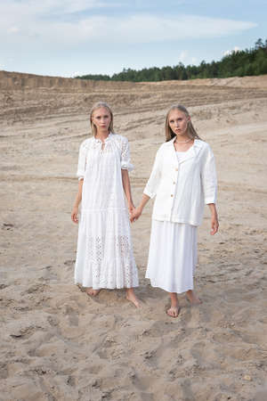 two attractive young twin sisters posing in sand quarry in elegant white clothes