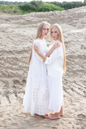 two attractive young twin sisters posing at sand quarry in elegant white clothes