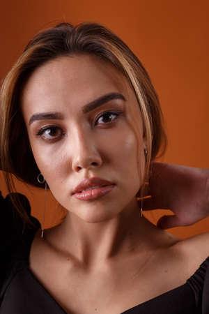elegant model wearing black dress with deep neckline posing on orange background Banque d'images