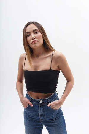 young attractive asian woman with long hair in black top, blue jeans on white