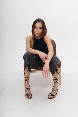 young attractive asian woman with long hair in black clothes sitting on chair 스톡 콘텐츠