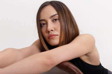 portrait of young attractive asian woman with long brown hair sitting on chair