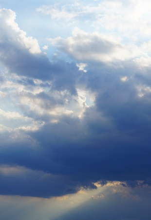 Dramatic dark sky with rays of sun coming through and light over the clouds Stock Photo