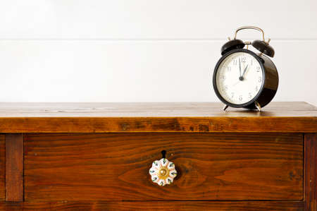 lunch hour: Retro alarm clock on bedside table,  background white wooden wall