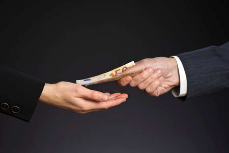 Business people hands and fifty euros banknotes, isolated gray background. Give a money, bribe. Corruption concept. Man and woman hand