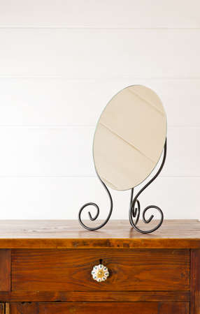 bedside: Retro mirror on bedside table,  background white wooden wall