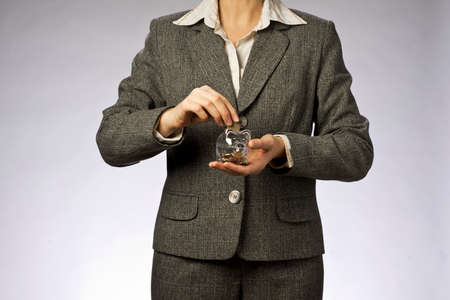 woman holding money: Business woman with gray jacket putting euro coin  into the  piggi bank. European finance currency. Woman holding money box