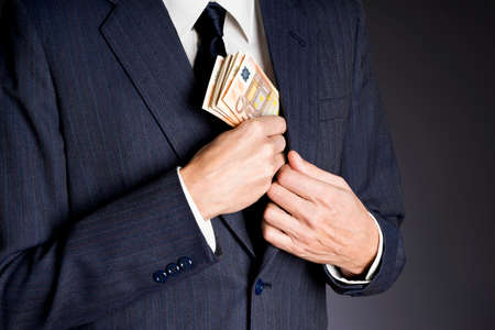 Business man in suit putting banknotes  fifty euros in his jacket breast pocket