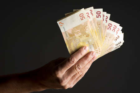 investment banking: Hand holding money - fifty euro banknotes isolated on a dark gray background Stock Photo