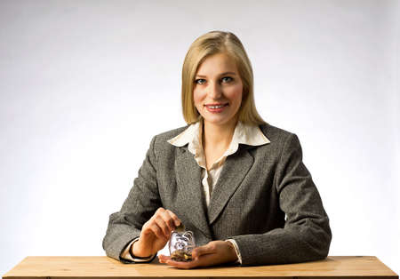 money box: Businesswoman sitting at office table and holding money box.  Business woman with gray jacket putting euro coin into the piggi bank. European finance currency. Stock Photo