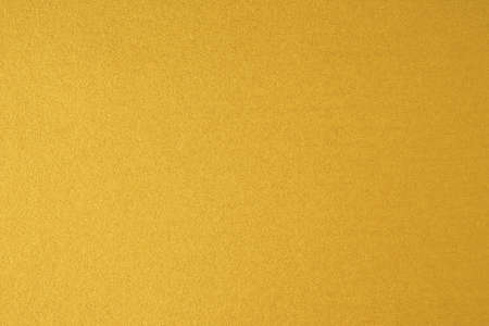 Glittering gold paper sheet texture background. Sparkling golden yellow pattern. Stock Photo
