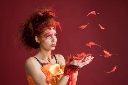bird feathers: Phoenix. Young girl portrait and flying feathers. Woman holds a feather in hands. Red background Stock Photo