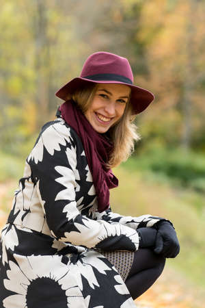 Woman in a floral patterned coat and wine red hat in the park. Happy girl and colorful autumn forest. Portrait of a lady, yellow, green, red and brown leaves background