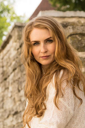 Caucasian white female model portrait, brick stone. Beautiful girl, long red hair, beige skirt and cardigan. Woman siting on the stairs in old town, limestone walls background