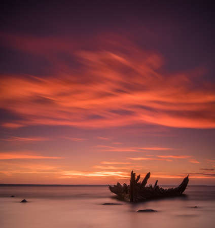 Old broken boat wreck on the shore, a frozen sea and beautiful red sunset background. Estonia, Europe. Stock Photo