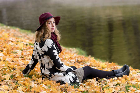 Woman in a floral patterned coat and wine red hat in the park, by the river. Happy girl and colorful autumn forest. Portrait of a lady, yellow, green, red and brown leaves background