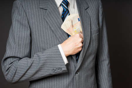 Businessman in suit putting banknotes in his jacket breast pocket. Business man is holding cash, stack of fifty euros money. Person pays in euro bills, isolated gray background. Stock Photo