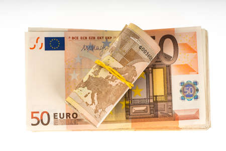 pile of money: Rolled up euros with rubber on the fifty euro banknotes pile. Money bunch stack