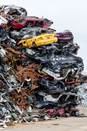 Dumping ground. Scrap metal heap. Compressed crushed cars is returned for recycling. Iron waste ground in the industrial area. Stacked automobile