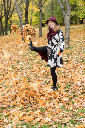 Woman in a floral patterned coat and wine red hat playing with leaves in the park. Happy girl throws maple tree leaves into the air. Yellow, green, red and brown leaves, colorful autumn forest