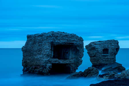 defense facilities: Liepaja beach bunker. Brick house, soft water, waves and rocks. Abandoned military ruins facilities in a stormy sea. Barracks building in the Baltic sea.  Liepaja, Latvia, Europe. Stock Photo