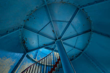 Old lighthouse on the inside. Red iron spiral stairs and blue wall. Kihnu, small island in Estonia. Europe Stock Photo