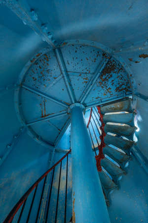 Old lighthouse on the inside. Red iron spiral stairs, round window and blue wall. Kihnu, small island in Estonia. Europe Stock Photo